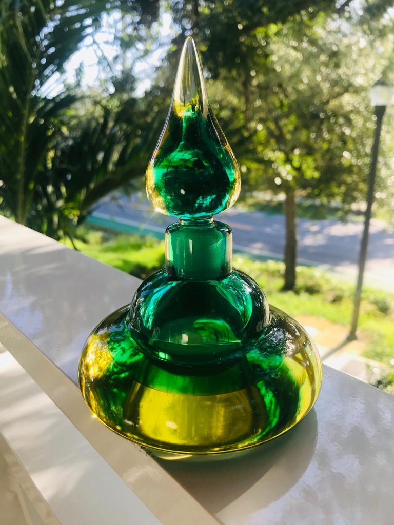 Mid-Century Modern decorative bottle or vintage perfume bottle by Flavio Poli for Seguso. Beautifully handcrafted in vibrant hues of emerald green and golden yellow. Hand blown with Sommerso technique featuring a stylized genie bottle design with a