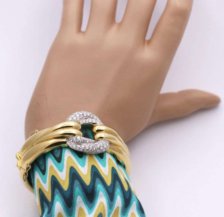 An 18K yellow gold, hinged cuff bracelet, with a contoured style, having a resemblance to fabric winding and twisting. At the center is another twisted design, however, this one is pave' set with 84 round brilliant cut diamonds. The diamonds weigh a