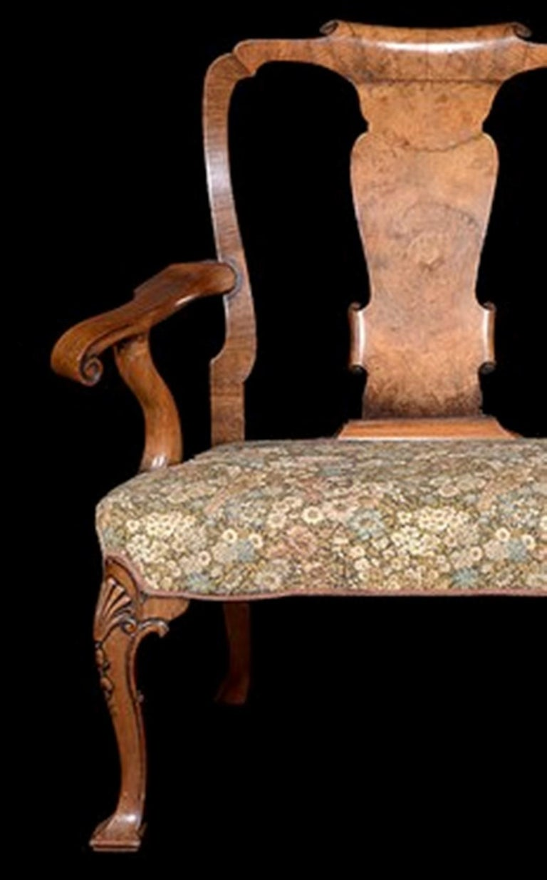 A Geo 11 style carved walnut chair-back sofa with vase shaped splats and scroll end arms.