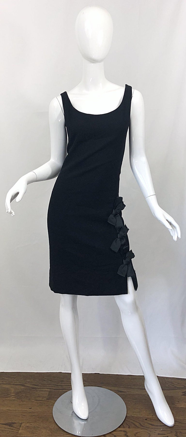 Timeless stylish 1960s GEOFFREY BEENE black wool bow detail sheath dress! Flattering sheath silhouette that looks great on any shape. Three black silk bows up the left hem. Hidden metal zipper up the side with hook-and-eye closure. Fully lined.