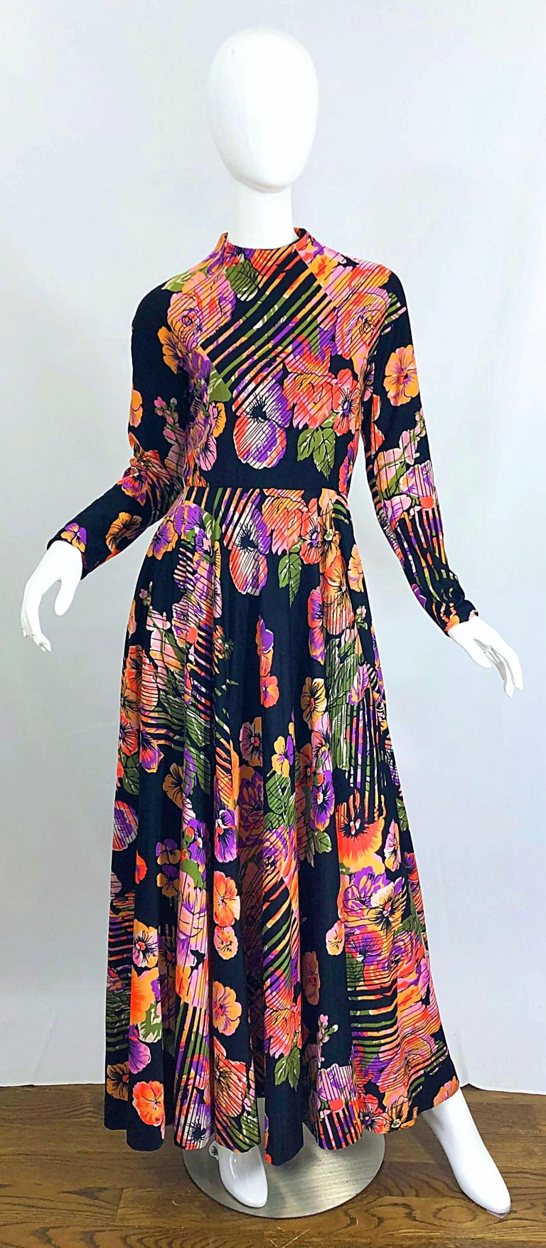 Fantastic vintage 1970s GEOFFREY BEENE abstract flower print long sleeve high neck jersey maki dress. Features floral prints in vibrant colors of purple, pink, peach, orange, green and white on a black background. Super soft double ply jersey