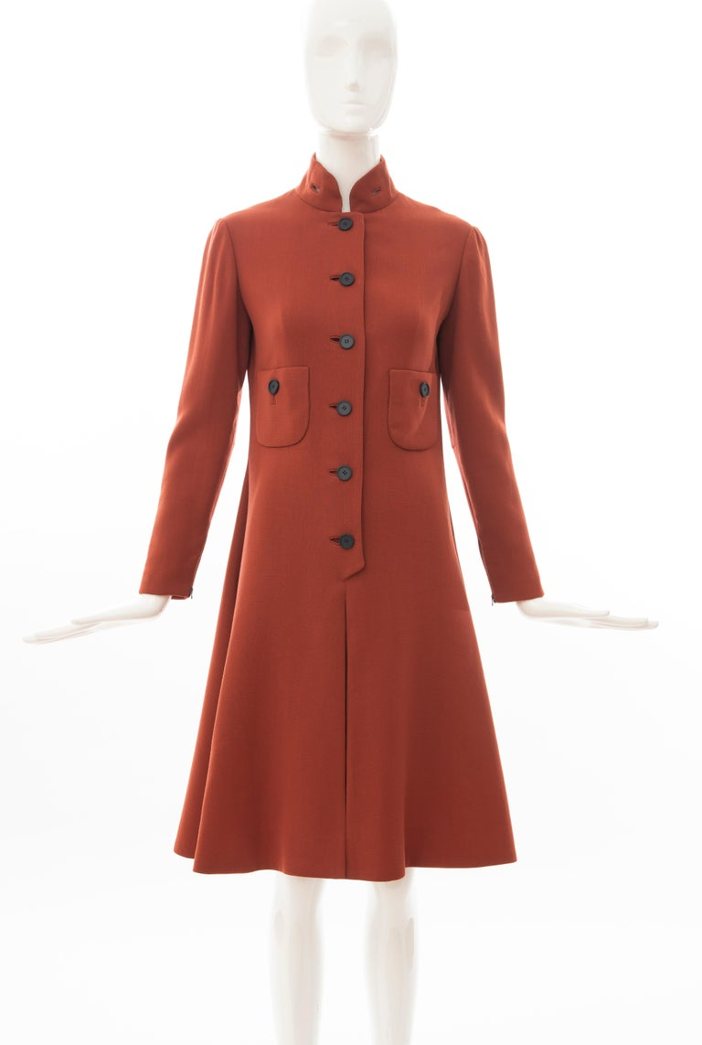 Geoffrey Beene, Circa 1960's cinnamon wool crepe princess style button front dress, nehru collar, two front pockets, long fitted sleeves with zipper closure and box pleated skirt.  No Size Label: Bust: 32, Waist: 29, Hip: 35, Shoulder: 15, Sleeve: