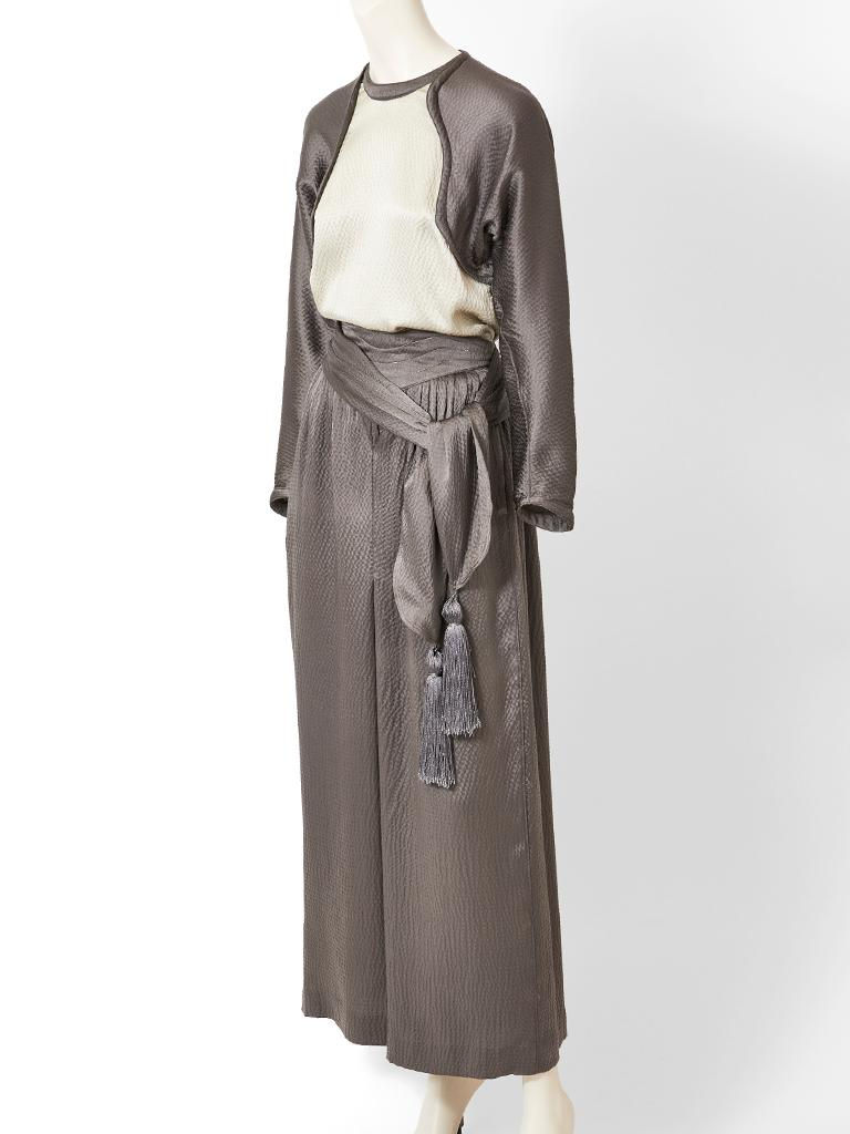 Geoffrey Beene,  pewter tone, hammered satin, top and palazzo pant ensemble. Top has a jewel neckline, with an ivory front panel and pewter tone dolman  sleeves. Pant is palazzo shape, in pewter with slight gathering at the waist. There is a wide