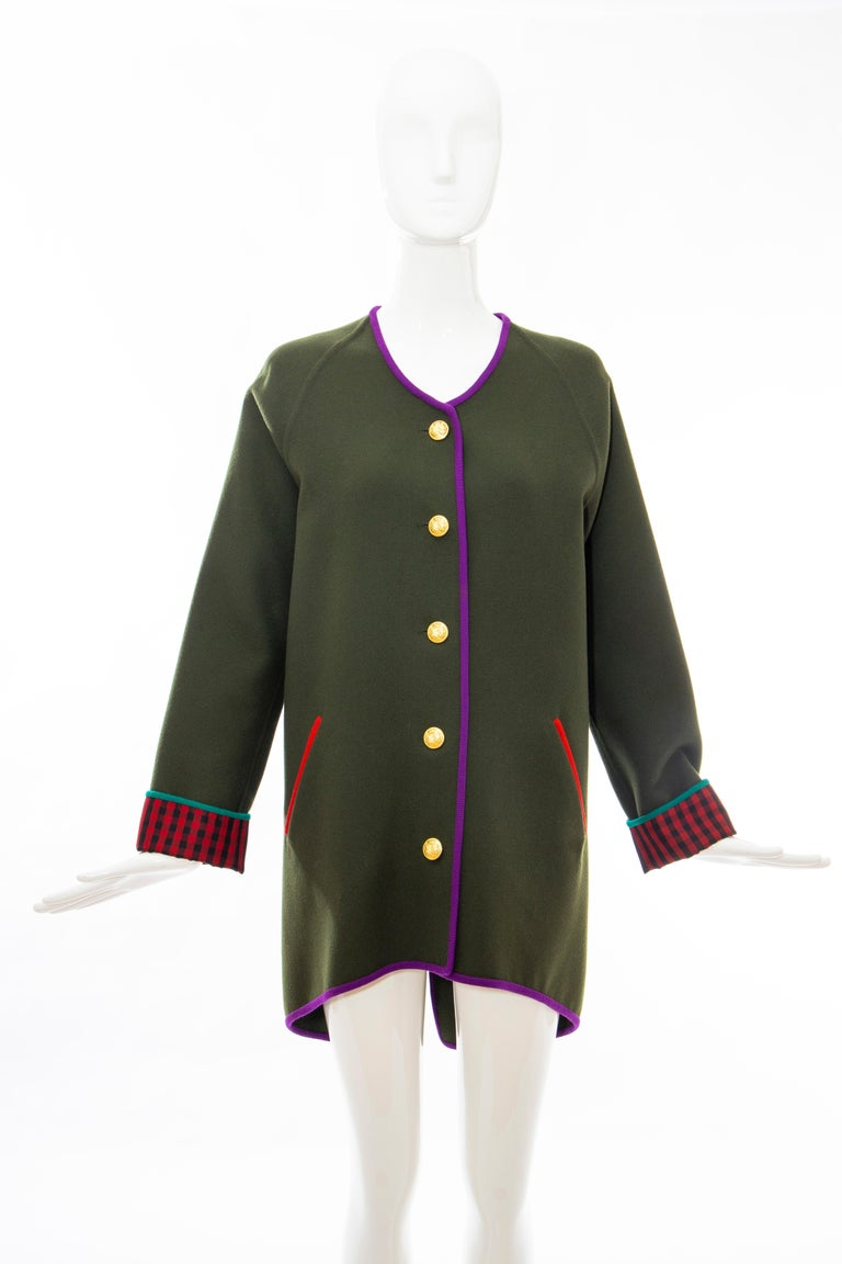 Geoffrey Beene Runway Fall 1988, olive green, wool, antique brass button front cutaway jacket with plum piping, two front red piping inset pockets and long check plaid cuffed dolman sleeves.   No Size Label  Bust: 39, Waist: 40, Hip: 41, Sleeve: 28,