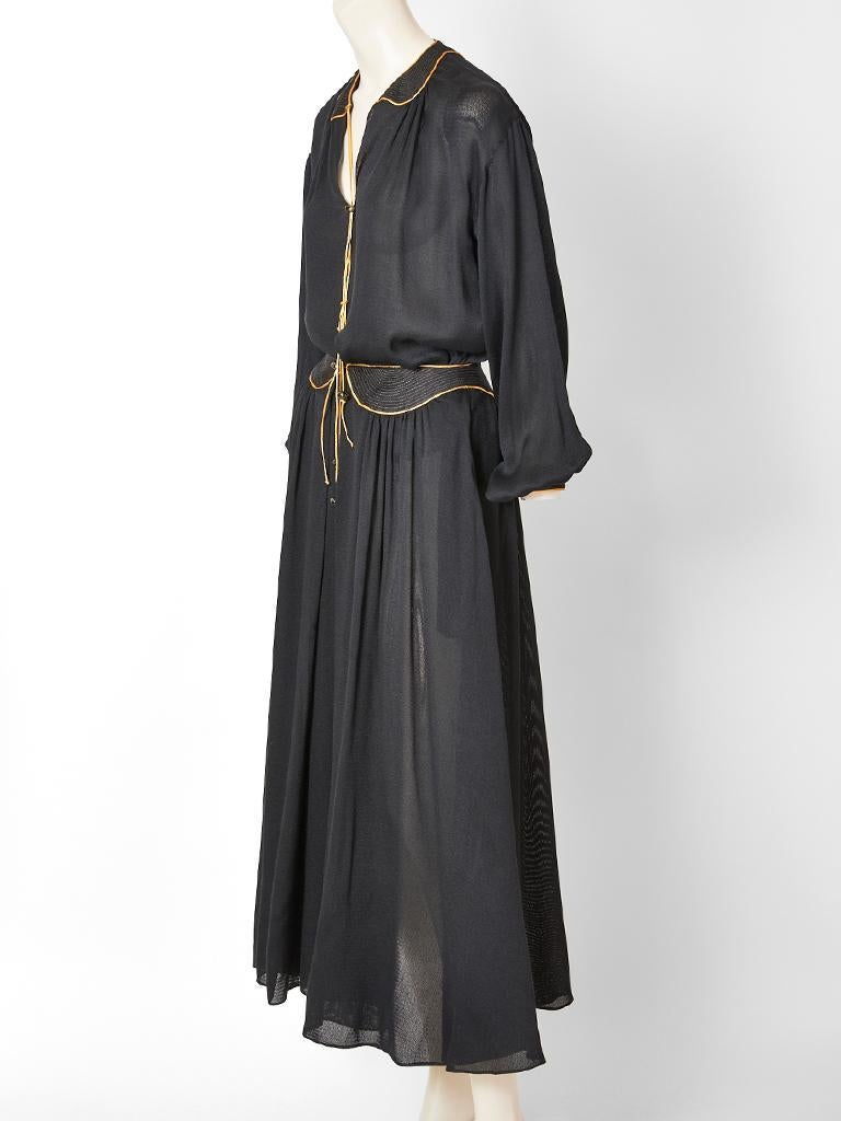 Geoffrey Beene, black, semi sheer, silk, skirt and blouse ensemble with gold details. Blouse is peasant style, having a v neckline with a peter pan collar that has gold stitching and tassel embellishment with balloon sleeves  and a dropped shoulder.