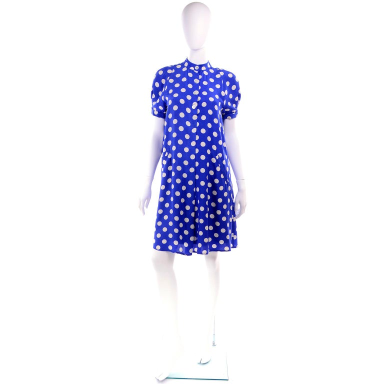 This is a lovely Geoffrey Beene vintage silk dress in a beautiful shade of royal blue with white polka dots.  The dress is similar to a tent dress, but not quite as full, and it has buttons in the front and side slit pockets.  There is a built in