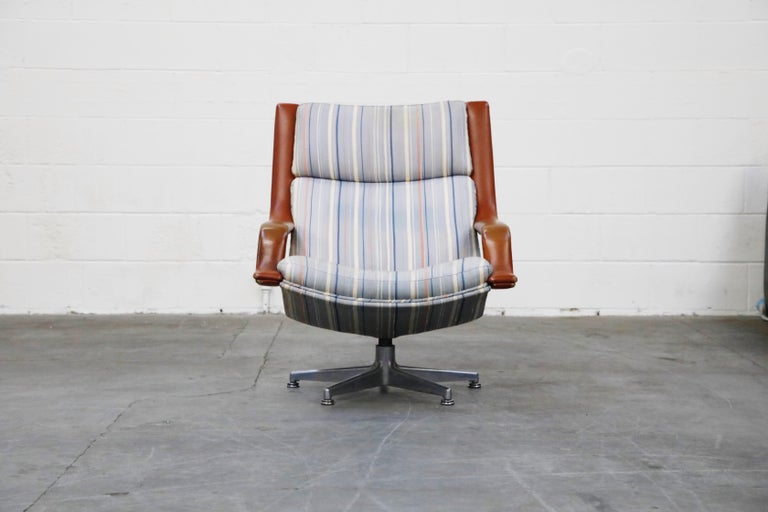 This laid-back swivel lounge armchair is model #F-140 by Geoffrey Harcourt for Artifort, Netherlands, circa 1970. Casual and stylish, this armchair has accentuated leather arms with striped fabric upholstery sitting atop a 5-star aluminum