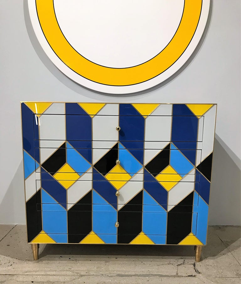 Unique geometric cobalt blue, ivory, black and yellow glass chest of drawers or commode with tapered brass legs and brass inlays. All four (4) drawers have a slow stop mechanism and lined in mirror with brass pull detail. Beautiful and solid