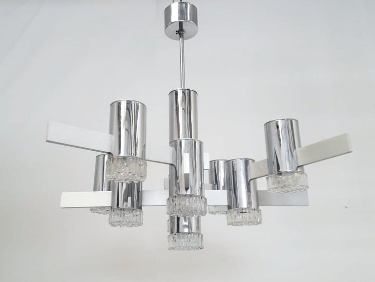 Vintage Italian chandelier with nine geometric glass diffusers mounted on polished chrome tubes and brushed aluminum arms, designed by Gaetano Sciolari / Made in Italy, circa 1970s 9 lights / E12 or E14 type / max 40W each Measures: Diameter 33