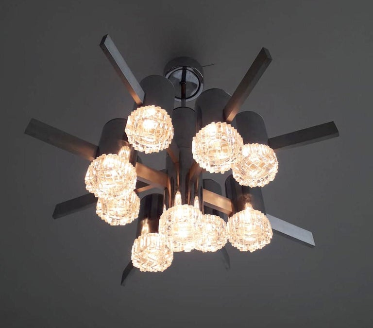 Vintage Italian chandelier with nine geometric glass diffusers mounted on polished chrome tubes and brushed aluminum arms, designed by Gaetano Sciolari / Made in Italy, circa 1970s 9 lights / E12 or E14 type / max 40W each Measures: Diameter 26