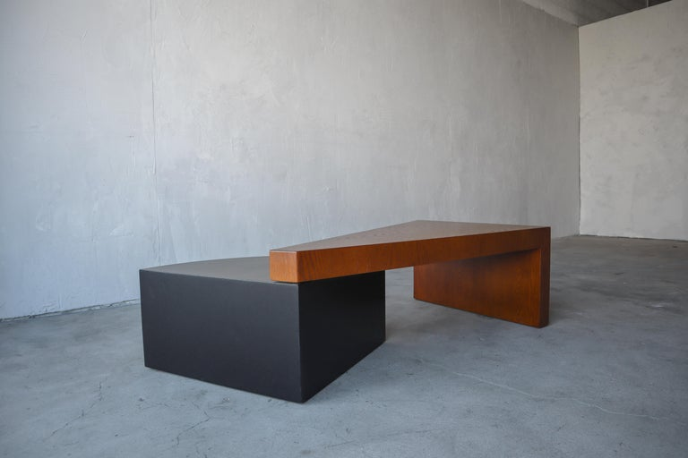 Great example of a post modern wood coffee table. Table is 2 tiered, comprised of a waterfalling triangular top supported at the opposite end by a lower tiered 1/4 circle drum. The entire table is oak, including the black drum. A very unique piece,