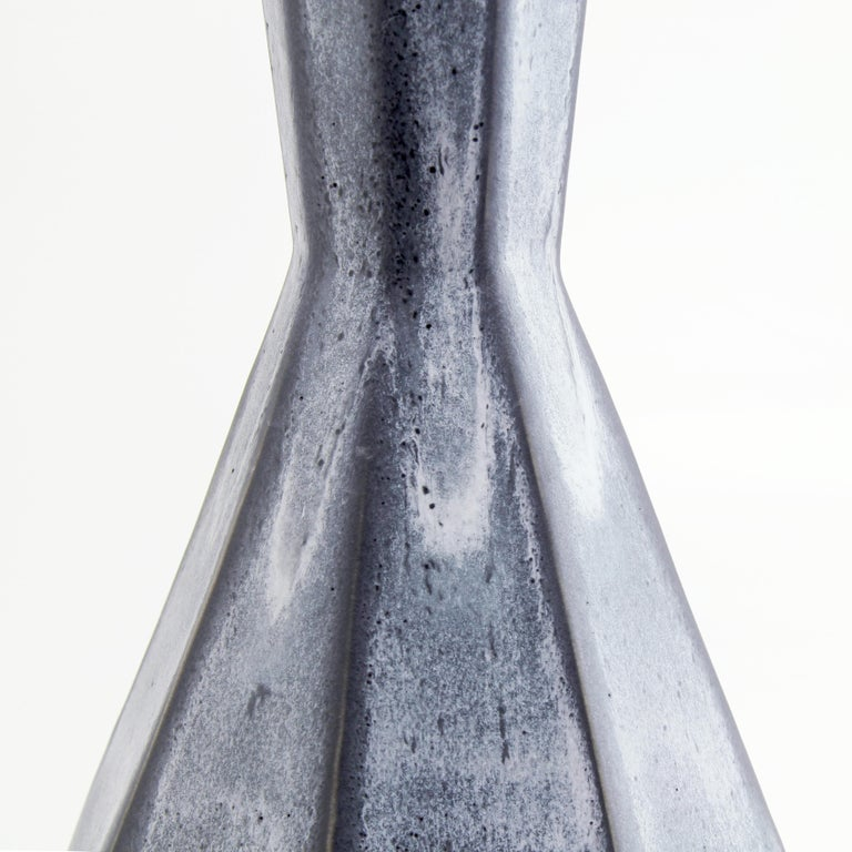The clean, modern design of the Geometric statement vase offers an updated, elegant look to your room with a Mid-Century Modern feel. This one of a kind vase features elegant grey and black matte glazes to highlight the clean faceted design. Add a