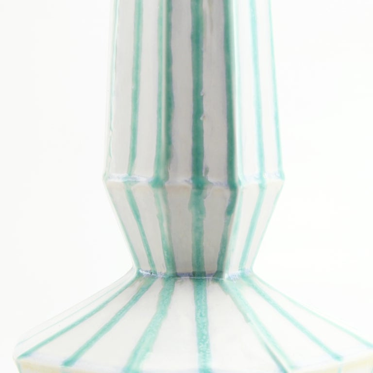 The clean, modern design of the geometric statement vase offers an updated, elegant look to your room with a Mid-Century Modern feel. This one of a kind vase features a modern stripe glaze to highlight the clean faceted design. Add a large