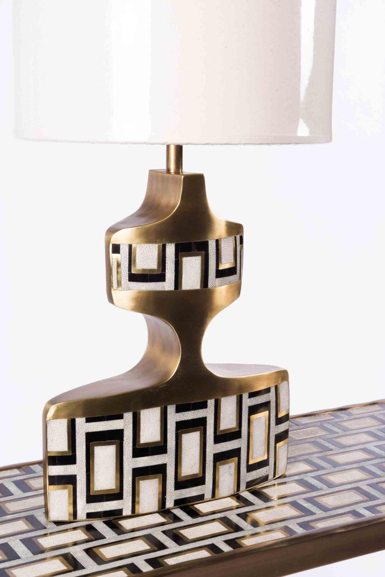 The geometric lamp is a sculptural piece with beautiful inlay detailing. This table lamp features a bold block pattern in a mixture of cream shagreen, black pen shell and bronze patina brass. Shade included. Available in a stripe pattern, image at