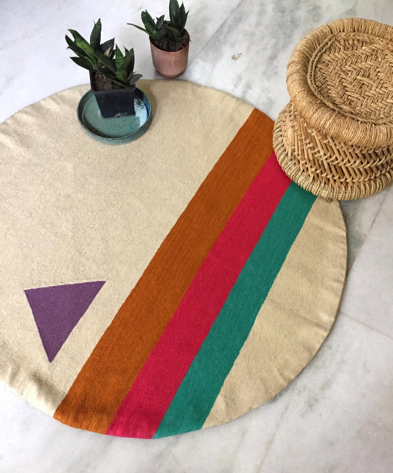 This modern round rug has been hand embroidered in the finest wool yarns by artisans in Kashmir, India, using a traditional embroidery technique which is native to this region.