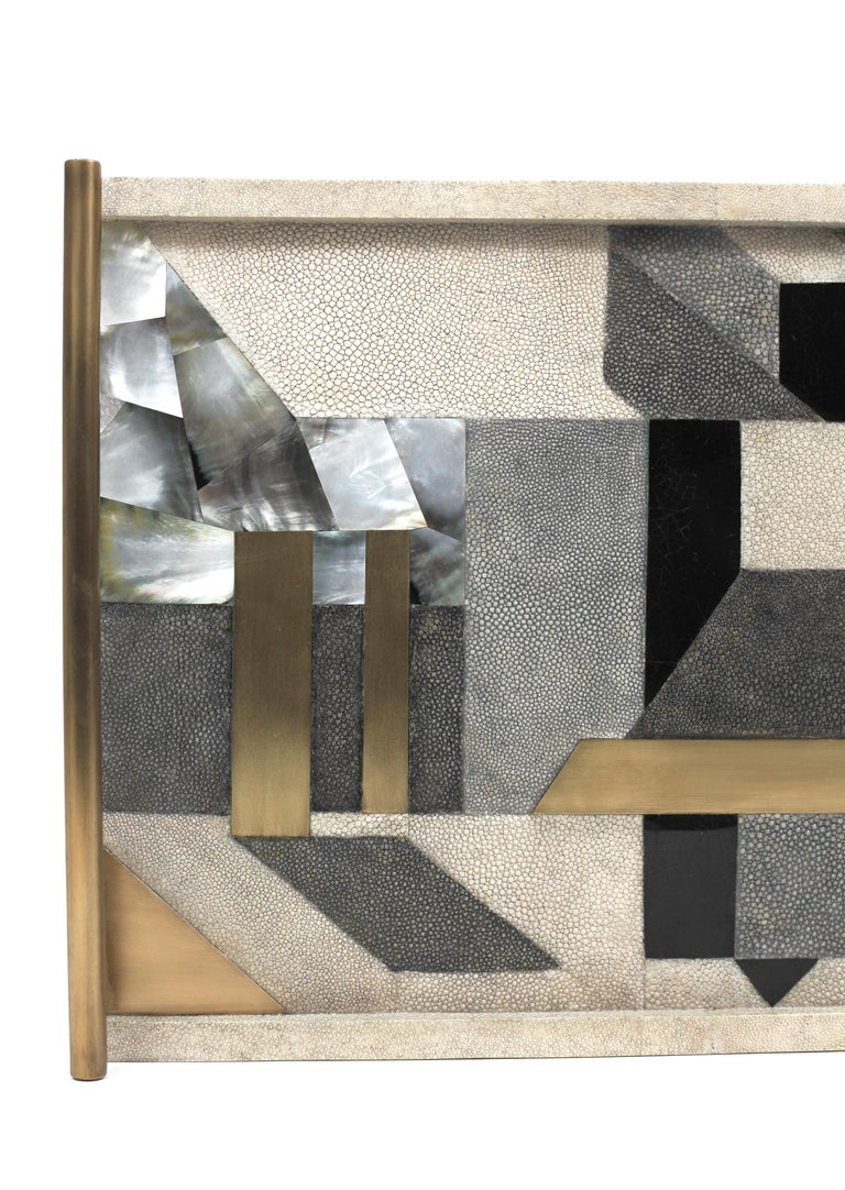 A classic rectangle tray revisited; this Kifu Paris geometric tray inlaid in a mixture of shagreen, shell and bronze-patina brass, makes for a stunning tabletop piece in any space. The brass handle are tubular. in Available in other sizes & finishes