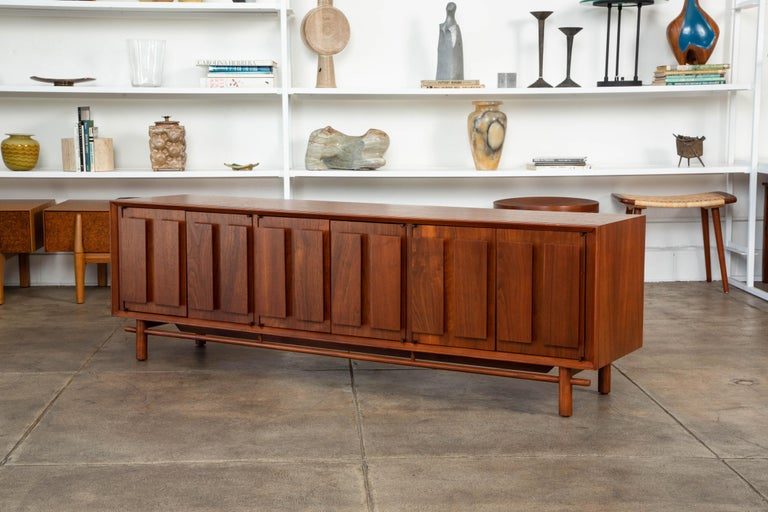 Walnut credenza by Lane Furniture Co., circa 1960s the cabinet features a walnut frame with beautiful grain, featuring three sets of side by side doors. Each door has two rectangular walnut panels decorating the front. The inside compartments have
