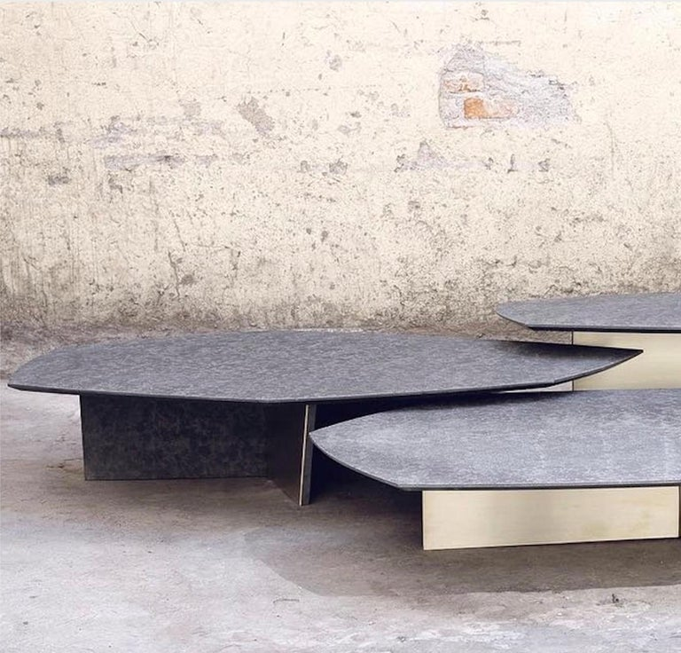 The Geometrik nesting coffee tables by Alexander Diaz Andersson has a satin brass base and a granite top.  Custom sizes available.  The aesthetic of this piece comfortably straddles the line between art and functionality, a philosophy that has