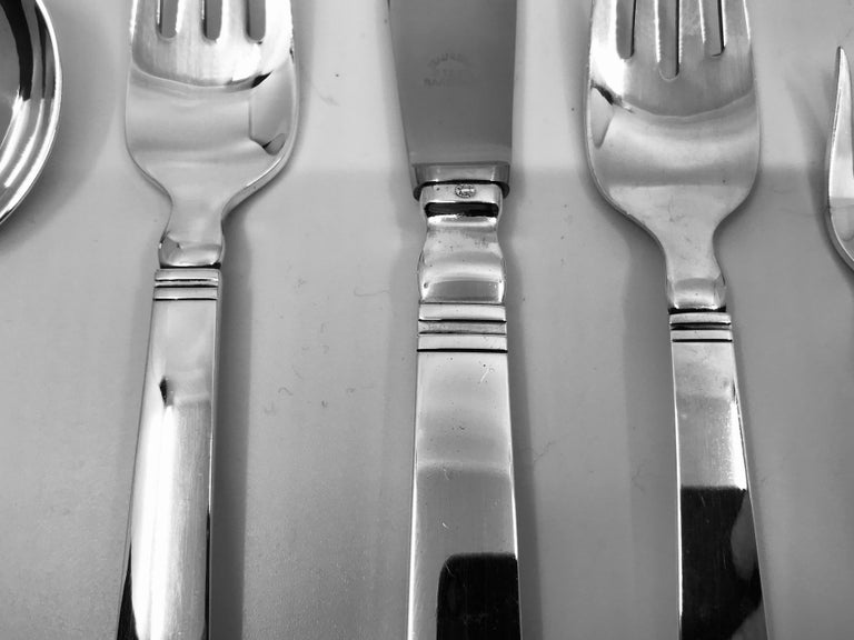This is a sterling silver Georg Jensen service in the Acadia pattern, design #46 by Ib Just Andersen from 1934. This service includes 12 settings of 8 pieces. 12 dinner knives 8 5/8