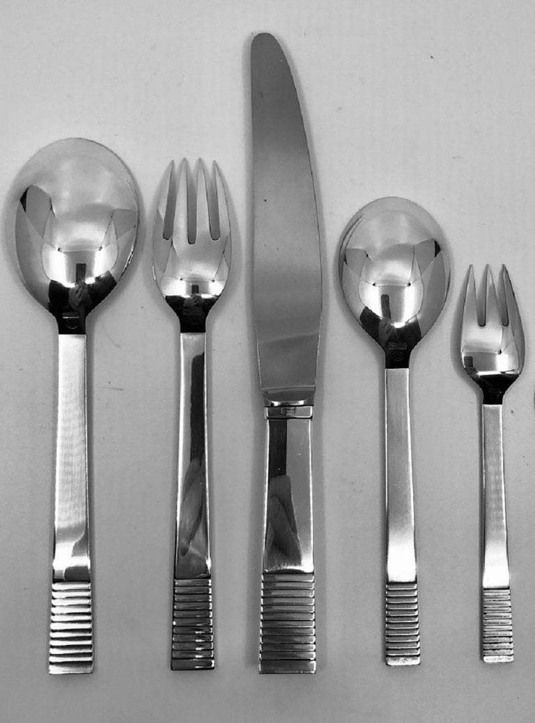 This is a Georg Jensen sterling silverware service in the Art Deco parallel pattern, design #25 by Oscar Gundlach-Pedersen from 1931.
