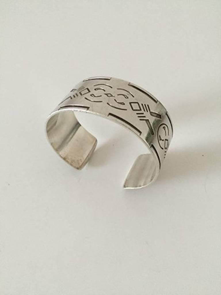 Georg Jensen Bangle, Sterling Silver Wide Cuff Design with Native American Motif #64. Designed by Harald Nielsen. Dates to after 1945. Measures 6 cm dia / 2 23/64 in. Weighs 43 g /