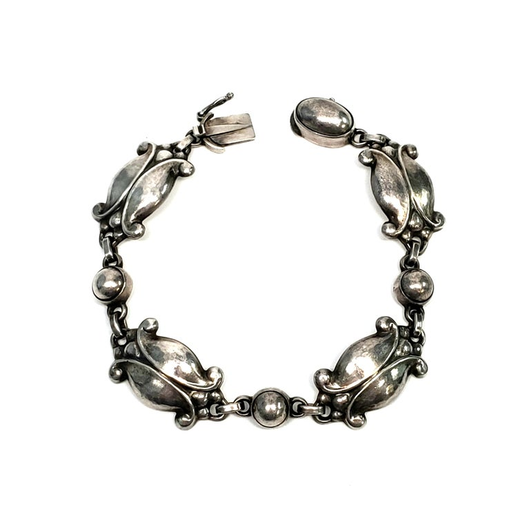 Vintage Georg Jensen sterling silver bracelet in the Moonlight Blossom pattern, #11, circa 1945.  The Moonlight Blossom pattern was designed by Georg Jensen himself, inspired by nature motifs, as is typical of Georg Jensen's work. This beautiful