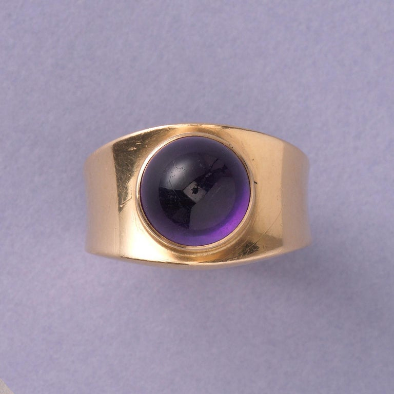 An 18 carat yellow gold band ring set with a cabochon cut amethyst, signed and numbered: Georg Jensen, 1124, Denmark, 1967.   weight 9.86 grams width: 2 cm ring size: 16.75 mm / 6 1/4 US