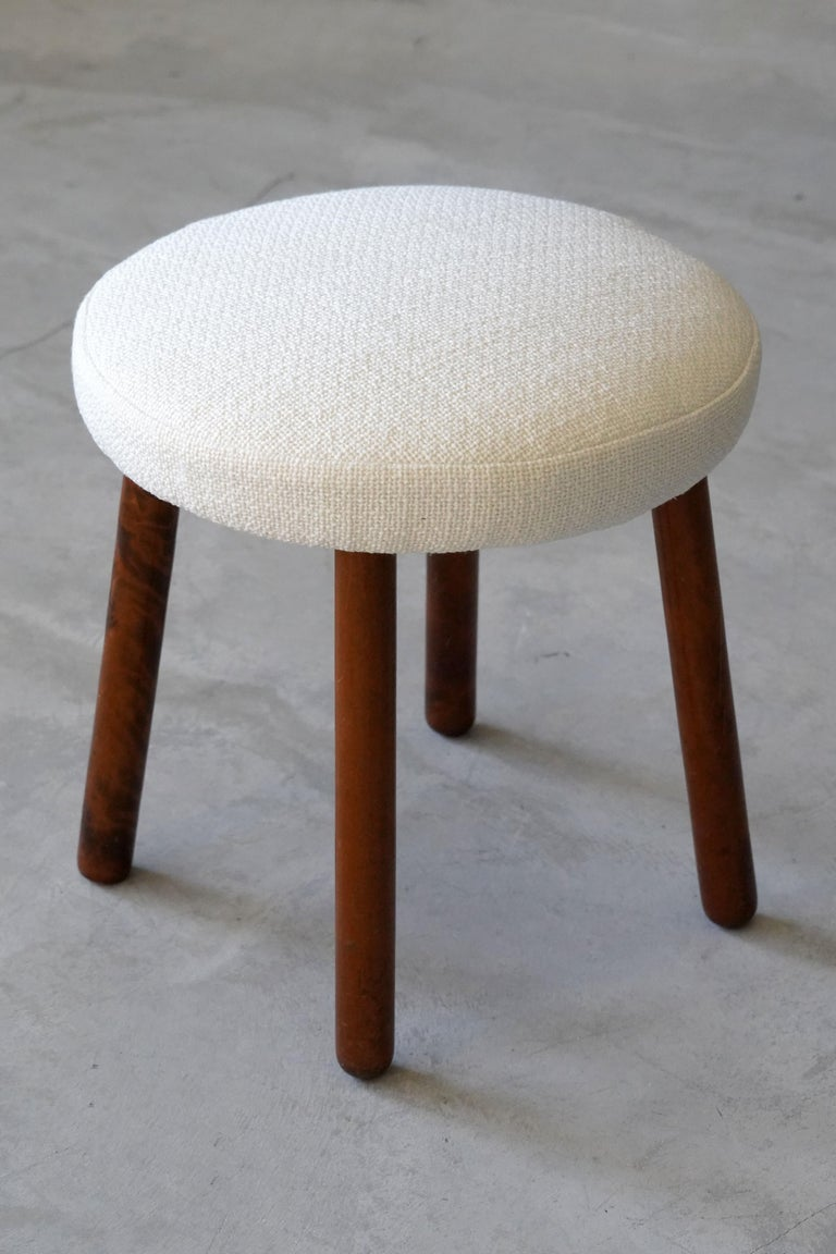 A stool, produced by Georg Kofoed. With dark-stained wooden legs. Reupholstered in brand new white fabric.   Other designers of the period include Philip Arctander, Arnold Madsen, Josef Frank, Viggo Boesen and Jean Royere.