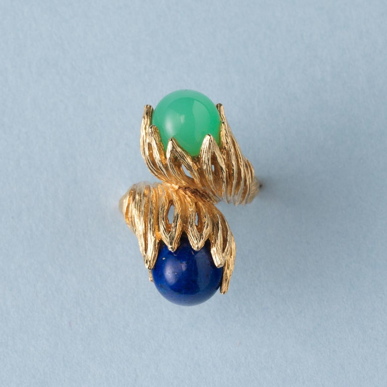 A sculptural 18 carat yellow gold ring with two textured leaves one is holding a lapis ball and one is set with a green calcedony ball, signed: Georg Lauer, Pforzheim, circa 1960-1970.  ring size: 16.5 mm / 6+ US. weight: 18.13 grams width: 2.1 – 30