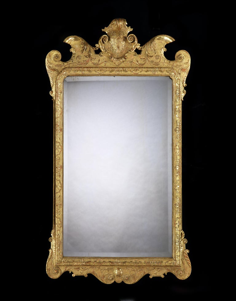 A George I carved and gilded gesso mirror with a stippled background and detailed carved foliage, the shaped cornice with a central cartouche, with bold scrolls to the sides. The 18th century bevelled plate surrounded by a frame similarly carved.