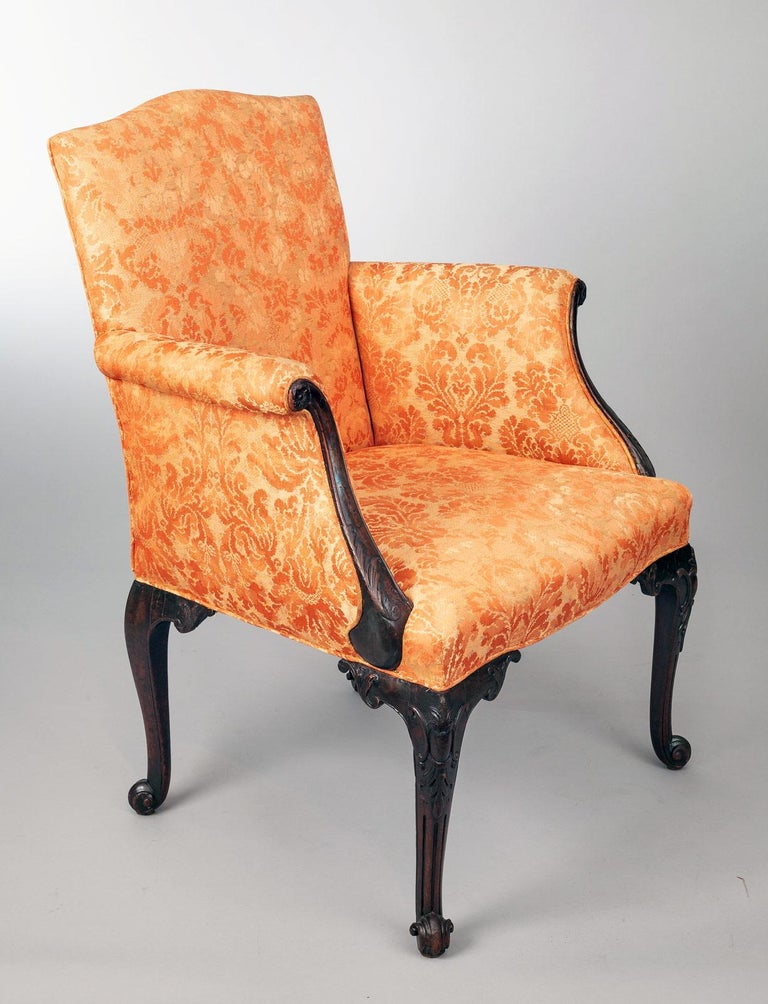 George II period bergere armchair with arched back rest, the outward scrolling arms framed by carved mahogany arm supports, above carved cabriole legs decorated with C-scrolls and a pineapple ending in a scroll foot. The back legs are also cabriole