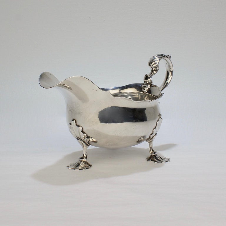 A superbly smithed George II sterling silver sauceboat.  With wonderful splayed feet, a shaped handle, and a slightly scalloped rim.  Hallmarked for George Hunter, Sterling, London and 1751.  Simply a fine piece of Georgian silver!  Length: ca. 8