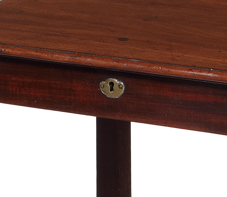The table has a rectangular molded edge top above a frieze drawer, on square section legs joined by a concave undertier, on castors.