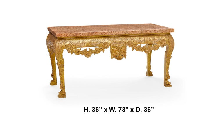 Impressive George II style finely carved giltwood console with thick marble top, meticulous attention to detail decorated with floral swags in the front and the sides centered with attractive large mask, resting on carved feet. Bearing a Sotheby's
