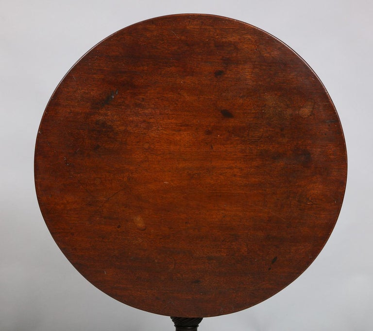 Good mid-18th century English mahogany tilt-top table with single plank circular top over balustrade turned shaft with spiral fluted urn base, the three cabriole legs ending in slipper feet, the whole possessing good rich color and patina.