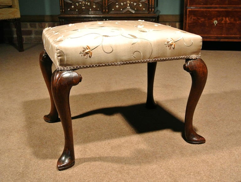A beautiful walnut stool, circa 1740 with elegant slipper feet and broad scrolled hips terminating in small roundels.  A good colour and condition and retaining original pine seat rails. Newly re-upholstered in a top quality pure silk heavyweight