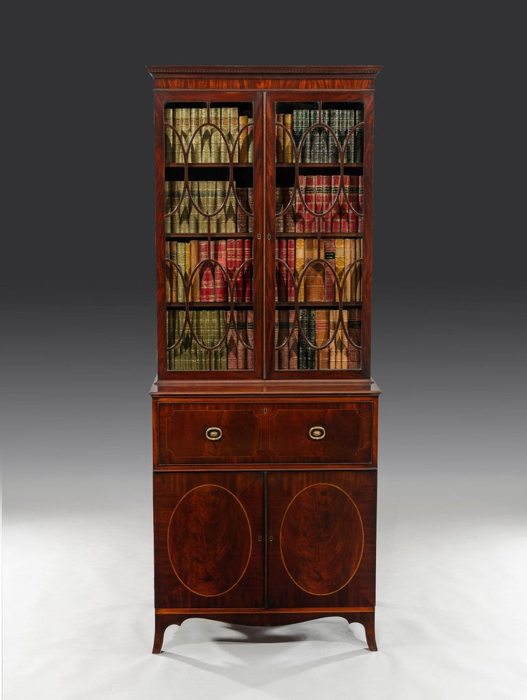 The rectangular dentil moulded cornice is surmounted on vertical cut mahogany veneers above a pair of oval-shaped astragal glazed doors enclosing three adjustable shelves. The lower section of the bookcase with a fully fitted secretaire drawer opens