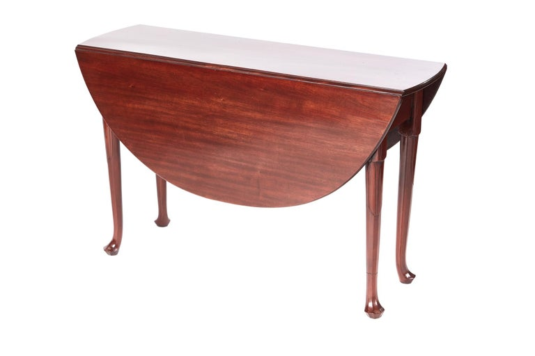 Quality George III mahogany dining table having an outstanding solid mahogany top with two drop leaves and supported by four unusual turned legs with pad feet.