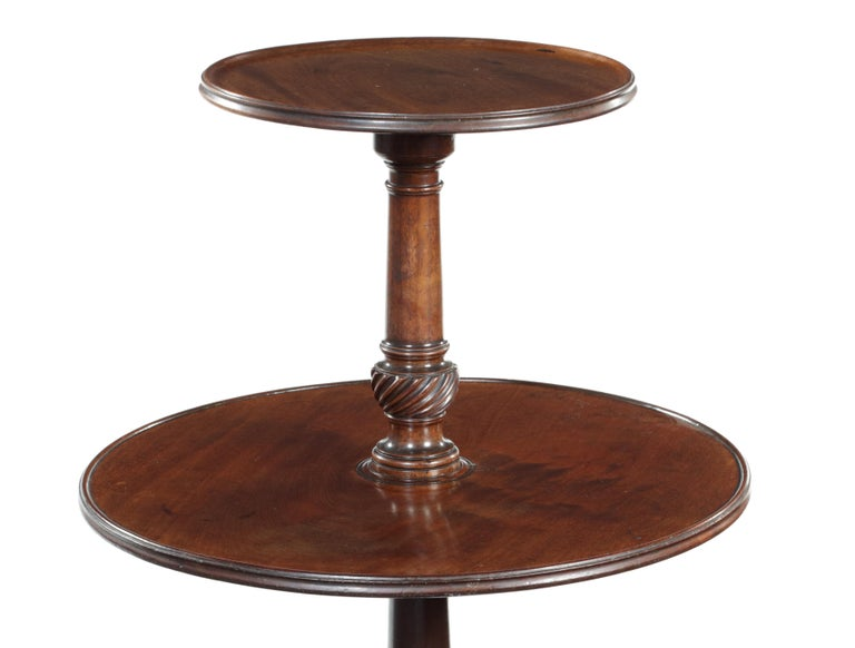George III carved mahogany two-tier dumb-waiter in the manner of Thomas Chippendale The circular moulded tops above ring turned and wreathed shafts on cabriole moulded downswept tripod legs with scroll feet, 60cm diameter, 89cm high.