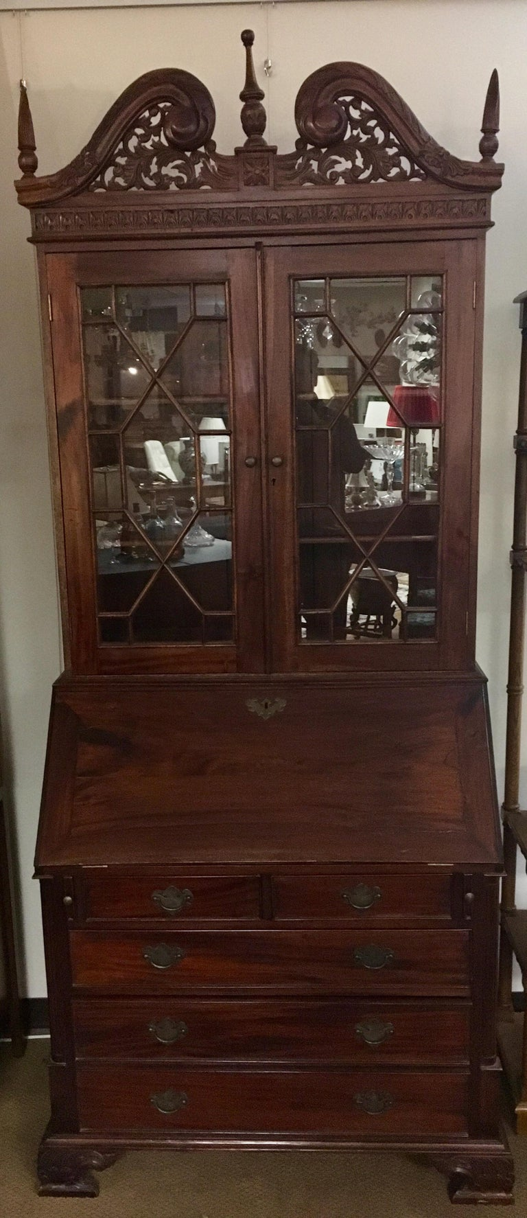 Early George III antique drop front secretary desk with gorgeous detail and multiple drawers and compartments. Features an intricately carved pierced pediment and finials and fretwork ove glass doors.