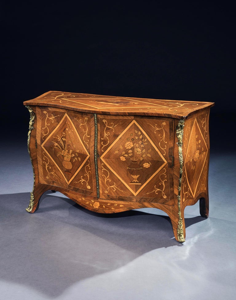 A George III bombé commode veneered in rosewood and hardwood, the cross banded top inlaid with scrolls and a central diamond form enclosing a marquetry panel depicting a musical score and various musical instruments. The lower part with a pair of