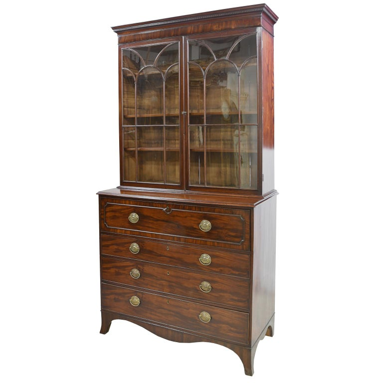 A stately George III secretary bookcase in fine, figured mahogany with inlaid mahogany banding on pull-out, drawer-front secretary. England, circa 1810. Bookcase is set back & has three adjustable shelves, with glazed doors that are decorated with a