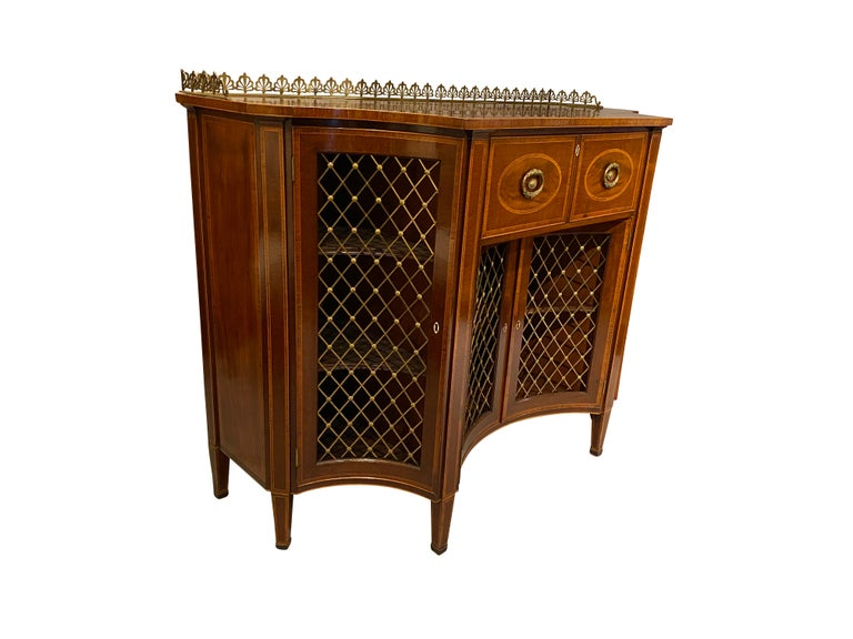 Most likely by Gillows of Lancaster. Rectangular top with concave corners, generous depth, with drawer opening to expose a fitted desk with drawers and cubbys over a pair of grill doors with false side doors, raised on square tapered legs. A finely