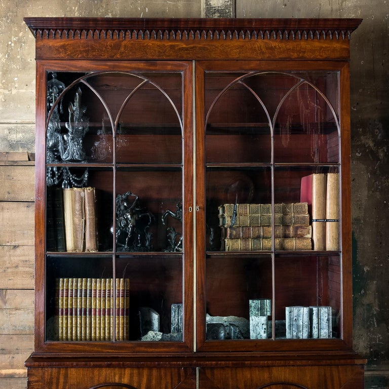 A late George III Mahogany bookcase, the moulded cornice above frieze hung with gothic pendants, the gothic glazed doors with astragal bars moulded as cluster columns, above base with oval panels to the doors enclosing an arrangement of drawers