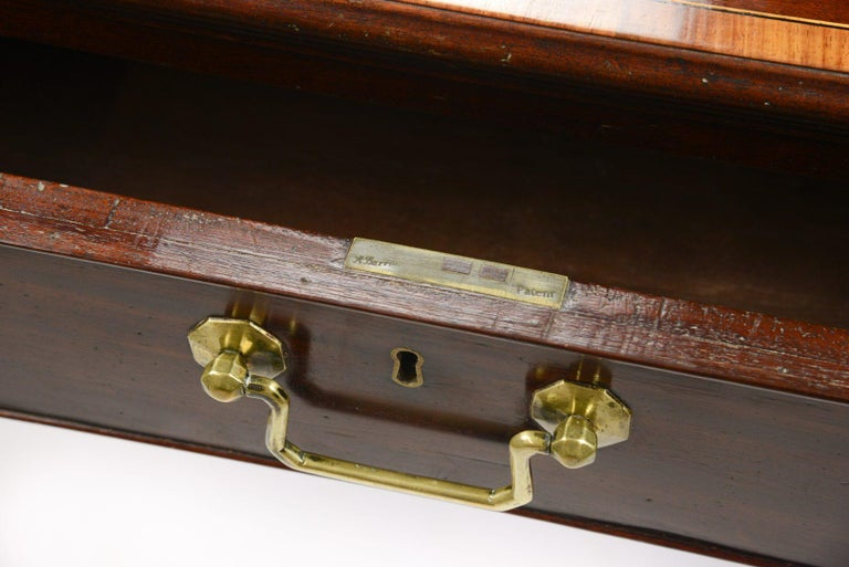 A George III plumb pudding mahogany library table, 1770-1780 the top cross-banded in tulipwood and line inlaid, all four sides fitted with drawers or blind drawers, original locks and handles.  The library table has draws on two opposing sides so