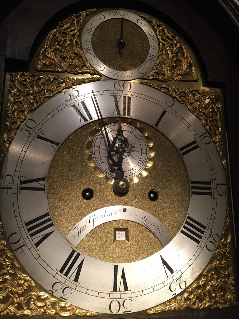 A fine George III period mahogany 8-day longcase clock with figured mahogany case. The hood with brass capped corner columns, arched top with 3 brass spire finials, interspersed by a scalloped edge decoration.  The arched brass dial is signed on