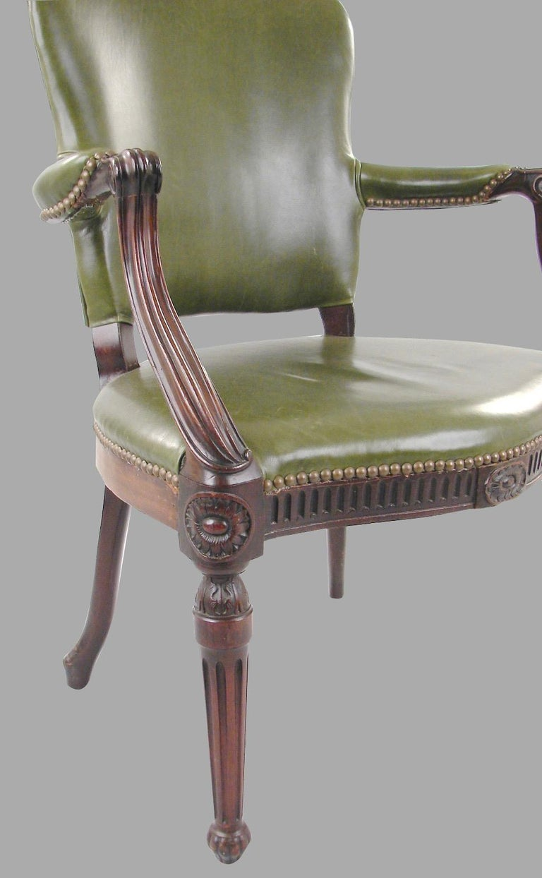 A George III mahogany leather upholstered open arm chair in the French Hepplewhite taste with nailhead trim, the serpentine front rail supported on reeded front legs with down swept rear legs, circa 1800.