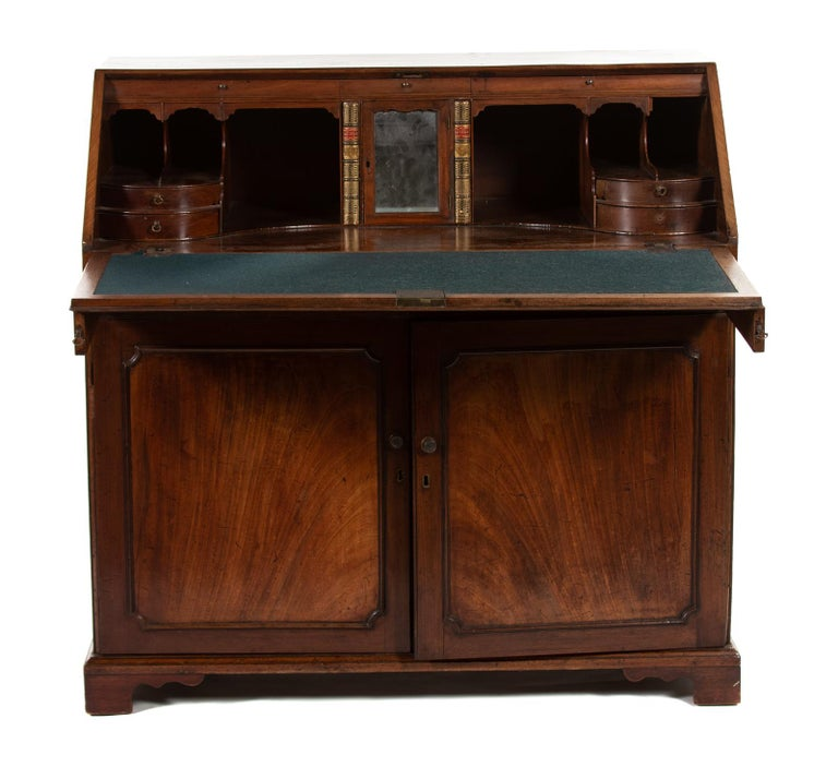 A George III mahogany slant-front desk Third quarter of the 18th century the rectangular top above a slant front enclosing drawers and fitted compartments, over a long drawer above a pair of cupboard doors enclosing two later sliding shelves,