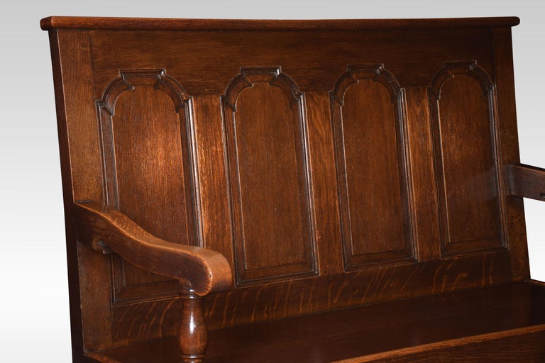 George III style oak bench settle. The four arched panelled back to the outswept armrests above the solid oak seat. All raised up on cabriole front legs. Dimensions Height 45 inches Width 55 inches Depth 26 inches.