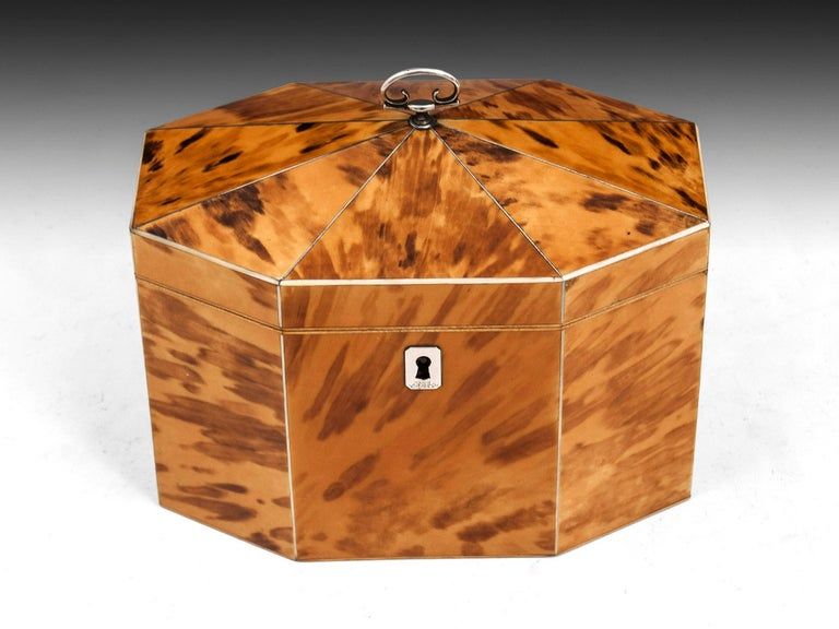 The octagonal shaped domed caddy top is inlaid with sterling silver stringing and has a scrolled silver handle. The tortoiseshell is inlaid with bone and the top opens to reveal the original lids and interior. The body of the tea caddy has a